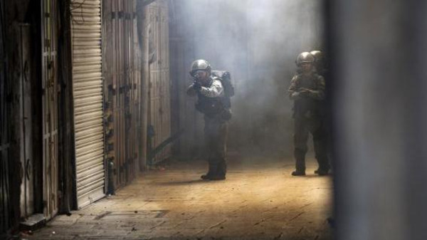 An Israeli policeman aims his weapon during clashes with Palestinians inside the old city of Jerusalem.