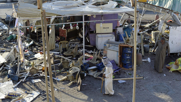 People walk past the site of Wednesday's car bomb attack in Baghdad's Sadr City October 9, 2014.