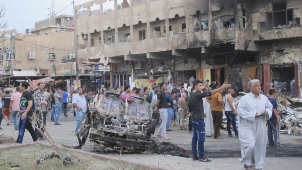 People gather at the site of a car bomb attack in Baghdad, October 16, 2014.