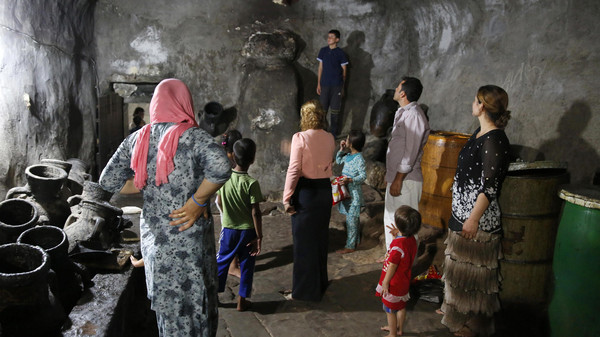 Displaced people from the minority Yazidi sect, who fled violence in the Iraqi town of Sinjar, worship at their main holy temple Lalish in Shikhan.
