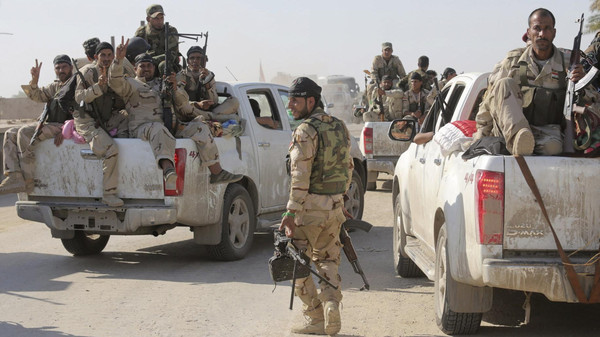 Fighters and Iraqi army members ride in vehicles during a patrol in Jurf al-Sakhar October 25, 2014.