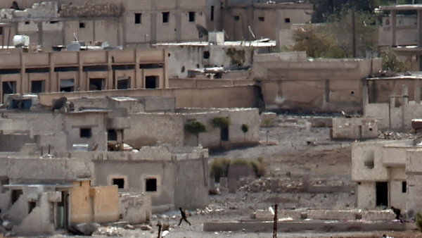 ISIS militants run for cover in Kobane after a U.S.-led coalition strike as seen from the Turkish-Syrian border in the southeastern village of Mursitpinar in the Sanliurfa province on October 15, 2014.