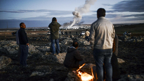 Kurdish people observe smoke rising from the Syrian town of Kobane, also known as Ain al-Arab, following an explosion as seen from a southeastern Turkish village on October 20, 2014.