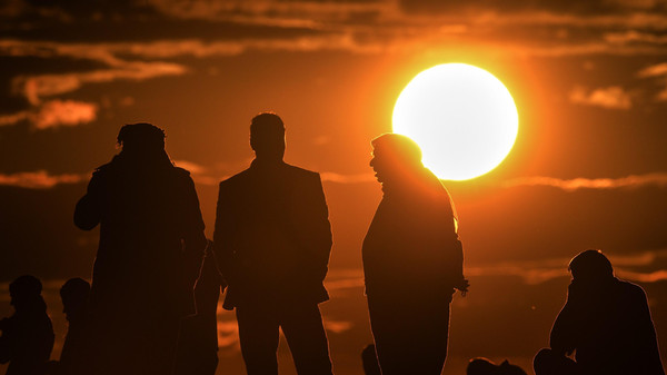 Kurdish people watch the Syrian town of Kobane, also known as Ain al-Arab, at sunset from the southeastern village of Mursitpinar, Sanliurfa province, on October 19, 2014.