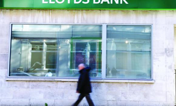 A man walks past a branch of Lloyds Bank in London.
