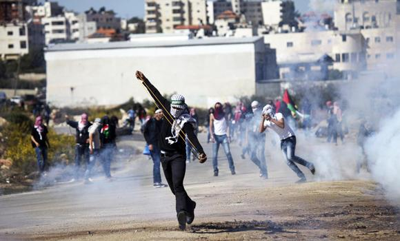 Palestinian protesters hurl stones toward Israeli troops during clashes at a protest outside the Ofer military prison, near the West Bank city of Ramallah, on Oct. 21, 2014, in solidarity with demonstrators at the Al-Aqsa mosque in Jerusalem.