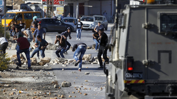 Palestinian youths from the Jalazoun refugee camp clash with Israeli security forces on a road at the entrance of the Jewish West Bank settlement of Beit El, north of Ramallah.