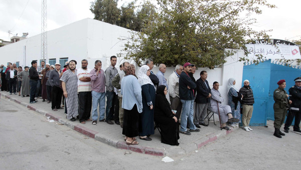 People wait in line outside a polling station to vote in Tunis October 26, 2014.