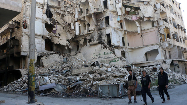 Rebel fighters walk past a heavily damaged building on October 23, 2014.