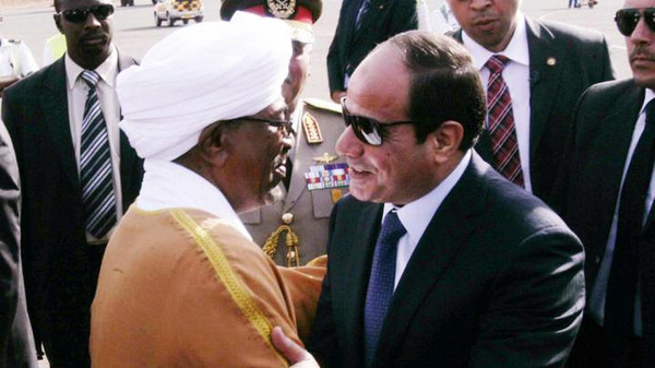 Sudanese President Omar al Bashir (L) welcomes Egyptian President Abdel Fattah al-Sisi upon his arrival at Khartoum airport for an official visit on June 27.