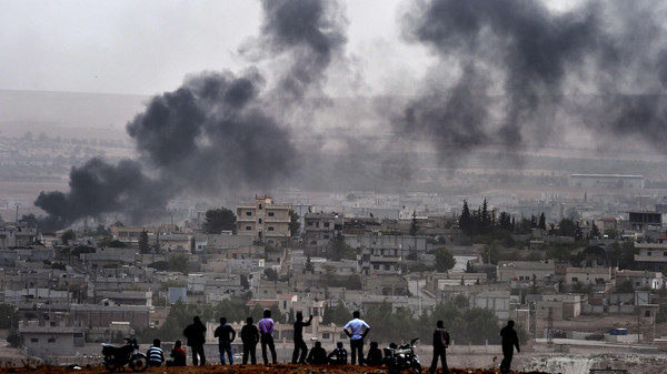 Kurdish people look at smoke rising from the Syrian town of Ain al-Arab, known as Kobane by the Kurds, from the Turkish-Syrian border, on October 11, 2014.