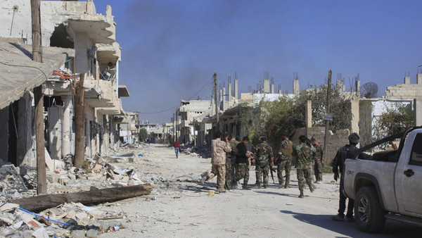 Smoke rises as forces loyal to Syria's President Bashar al-Assad gather along a damaged street in the town of Morek after regaining control of the area October 24, 2014.