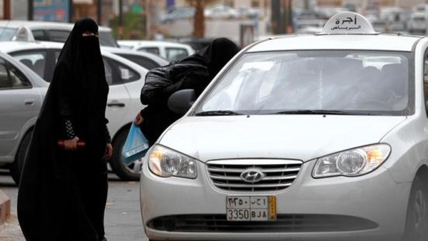 A Saudi woman stands next to a taxi in Riyadh.