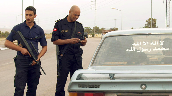 Tunisian security forces check the identification card of a driver on October 15, 2014 in Kasserine.