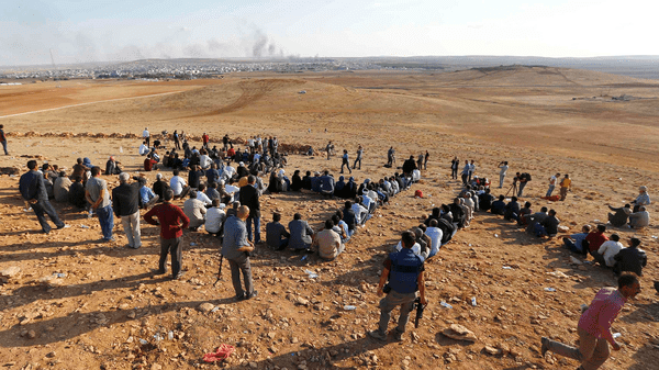 Turkish Kurds gather on the hill near the Mursitpinar border crossing on the Turkish-Syrian border near the southeastern town of Suruc in Sanliurfa province to support Kurdish fighters in Kobane October 15, 2014.