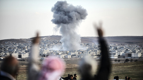 A picture taken from the southeastern Turkish village of Mursitpinar in the province of Sanliurfa shows people gesturing as smoke rises in the sky following an attack by jet aircrafts in the Syrian town of Kobane, also known as Ain al-Arab, on Oct. 22, 2014.