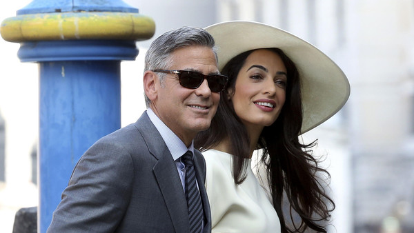U.S. actor George Clooney and his wife Amal Alamuddin arrive at Venice city hall for a civil ceremony to formalize their wedding in Venice September 29, 2014.