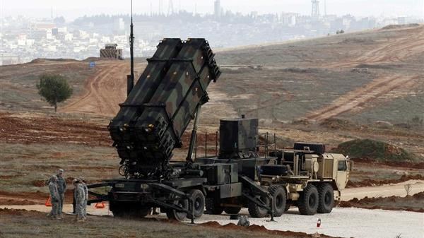 American soldiers wait beside a US Patriot missile system at a Turkish military base in Gaziantep, on Feb. 5, 2013.