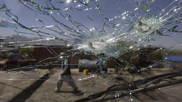 An Afghan man walks next to the cracked side window of a vehicle after was hit by a remote-controlled bomb in Kabul.