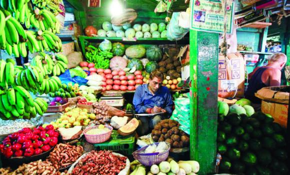 A vendor works at his vegetable stall at a wholesale fruit and vegetable market in Mumbai.