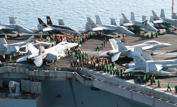 In this photo taken Oct. 10, 2014, US sailors conduct a drill on the aircraft carrier USS George H.W. Bush in the Persian Gulf. US Navy jets have been pummelling Islamic State positions in Iraq and Syria over the past two weeks.