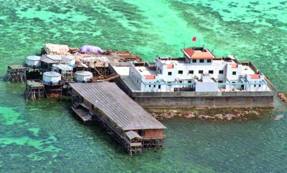 A Chinese flag flies from one of the two newly-finished concrete structures on the Mischief Reef off the disputed Spratlys group of islands in the South China Sea in this aerial Feb. 8. 1999, file photo.