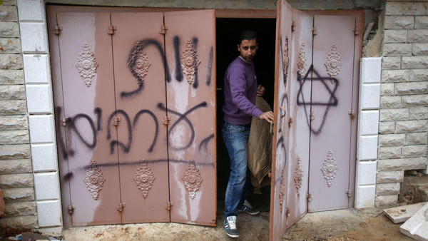 A Palestinian man inspects a door at the Hamayel family that bears Hebrew writing which reads 'Death to Arabs,' after an attack by suspected Jewish extremists, in a village northeast of Ramallah, on November 23, 2014.