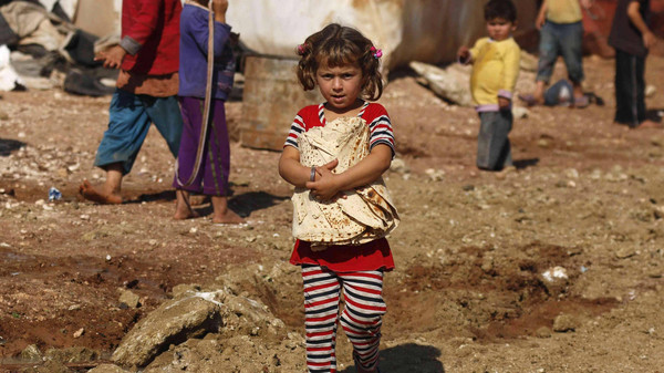 A Syrian refugee girl carries bread as she stands outside tents in the Bab Al-Salam refugee camp in Azaz, near the Syrian-Turkish border, October 27, 2014.