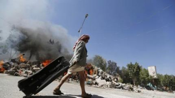 A man pulls a suitcase past demolished huts set on fire, as he leaves Taghyeer (Change) Square in Sanaa November 10, 2014.