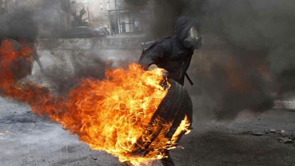 A masked Palestinian protester carries a burning tire during clashes with Israeli troops, following an anti-Israel demonstration over the entry restrictions to the al-Aqsa mosque, near the West Bank city of Ramallah October 31, 2014.