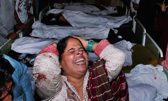 A woman mourns for her relative next to the bodies of bomb blast victims at a local hospital in Lahore, Pakistan, on Sunday.