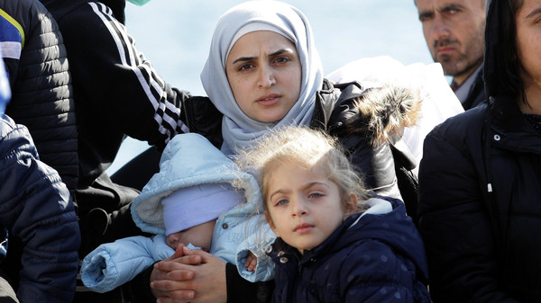 A woman with two children sits on a boat carrying migrants upon their arrival at the Cretan port of Ierapetra on Nov. 27, 2014.