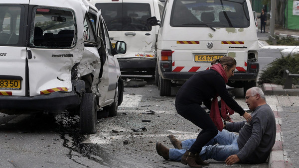 A wounded man sits on the street after an attack by a Palestinian motorist in Jerusalem November 5, 2014.