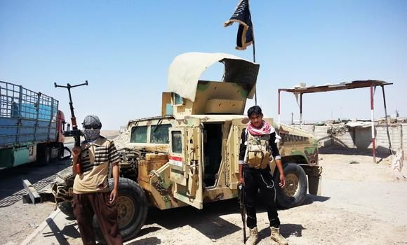 In this June 19, 2014 photo, al-Qaeda-inspired militants stand with captured Iraqi army Humvee at a checkpoint outside an oil refinery in Beiji, some 250 kilometers north of Baghdad, Iraq.