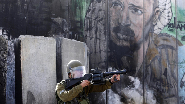 An Israeli soldier points his weapon toward Palestinian protesters during clashes following an anti-Israel demonstration at Qalandia checkpoint near the West Bank city of Ramallah Nov. 2, 2014.