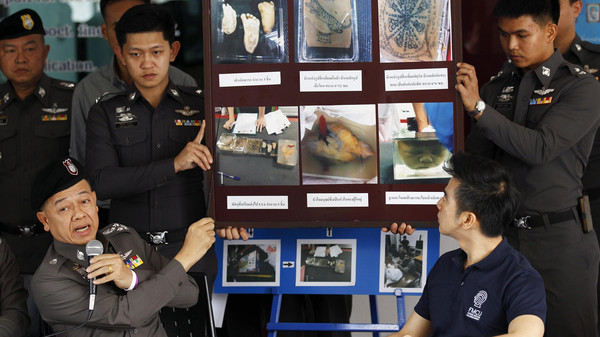 Policemen show pictures of body parts found in parcels as they address reporters in Bangkok November 17, 2014.