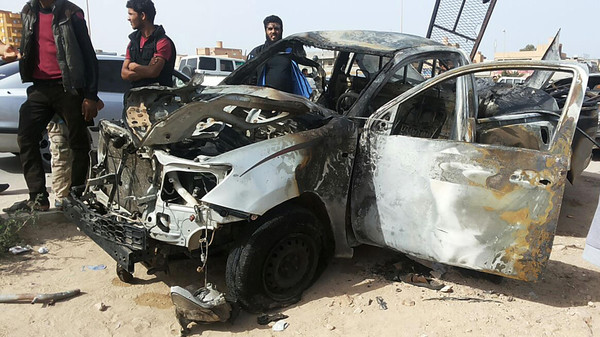 People stand at the scene of a car bomb explosion in the eastern city of Tobruk, near the Egyptian border.