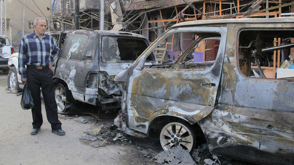 A man looks at the damage at the site of a car bomb attack in Baghdad Nov. 15, 2014.