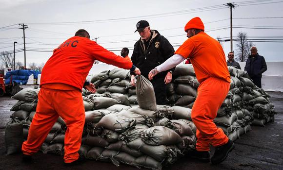 Erie County Holding Center inmates help pile sandbags to prepare for possible flooding following a massive snow storm in Williamsville, New York, on Sunday.