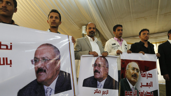 Journalists who support Yemen's former President Ali Abdullah Saleh carry posters bearing his image at the headquarters of his General People's Congress (GPC) party in Sanaa November 6, 2014.