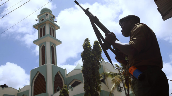 A police officer holds his position outside the Masjid Mussa mosque during an operation to to suppress demonstrators reacting to the killing of an Islamic cleric at Kenya's coastal city of Mombasa Oct. 4, 2013.