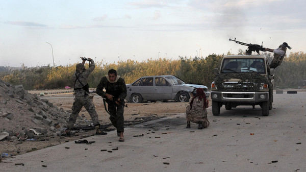 Members of the pro-government Libyan forces fire towards Islamist militiamen during a attack on districts held by the militias on Nov.3, 2014 around the port of eastern Libya's city of Benghazi.