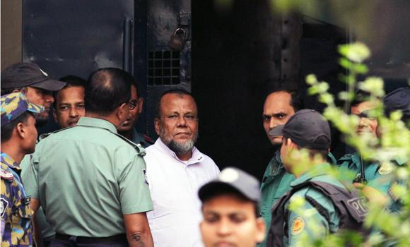 Bangladesh former ruling party official Mobarak Hossain (C) looks on as he enters a van at the International Crimes Tribunal court in Dhaka on Sunday. Bangladesh's war crimes court later sentenced him to hang for mass murder.