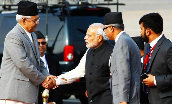 Nepalese Home Minister Bam Dev Gautam, left, welcomes Indian Prime Minister Narendra Modi, center, as he arrives at the Tribhuwan Airport to attend the 18th summit of South Asian Association for Regional Cooperation (SAARC) in Katmandu, Nepal, on Tuesday.