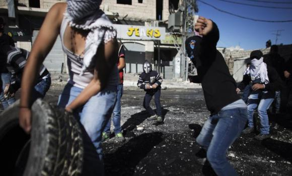 Palestinian youths throw stones towards Israeli border police during clashes.