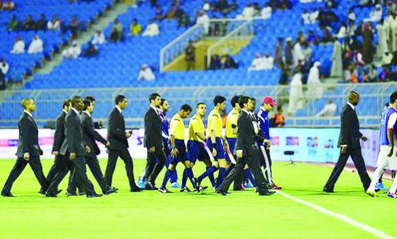 Policemen escort players from the ground after a Gulf Cup match.