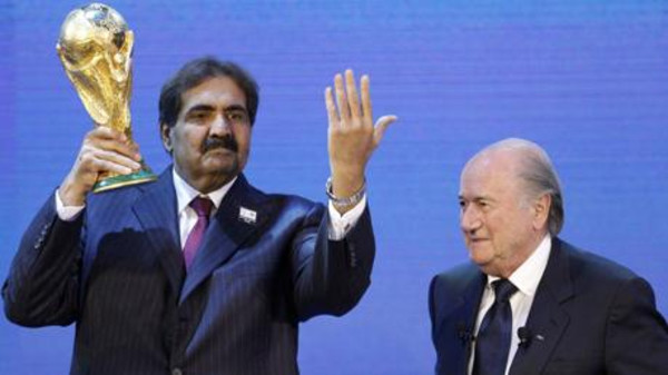 Qatar's former Emir Sheikh Hamad bin Khalifa al Thani (L) holds up a copy of the World Cup he received from FIFA President Sepp Blatter.