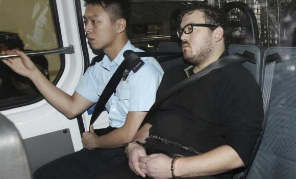 Rurik George Caton Jutting, 29, is escorted by a police officer in a police van before appearing in a court in Hong Kong on Monday.