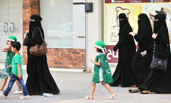 In this Sept. 23, 2013 file photo, Saudi women and their children walk along a street as they make their way to a celebration rally marking the 83rd Saudi Arabian National Day in the desert kingdom's capital Riyadh