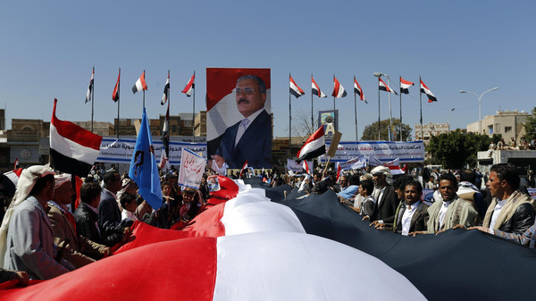 Supporters of Yemen's former President Ali Abdullah Saleh hold a huge Yemeni flag next to a poster of Saleh as they rally in his support in Sanaa Nov. 7, 2014.
